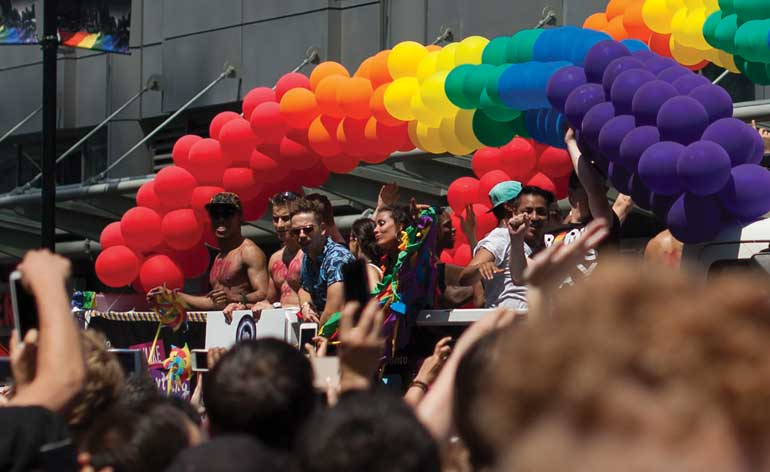 Attendees look on as the Pride parade makes its way through Dundas Square.