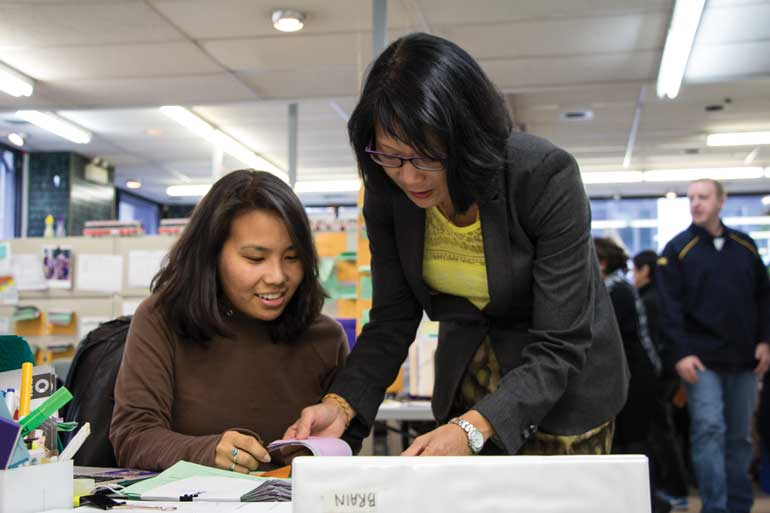 Toronto mayoral candidate Olivia Chow reviews voter recall slips with a volunteer in her campaign office. Chow now polls third for Oct. 27 mayoral election. Photo by Nick Westoll.