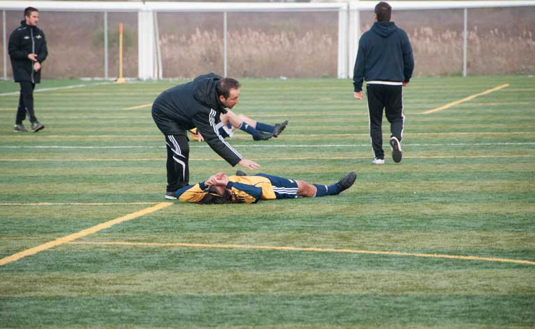 Humber Hawks assistant coach Alex Sabatini comforts Jesse Assing in extra time after a disappointing loss to Algonquin Thunder at Welland, Ont.  (Photo by Aaron D'Andrea)