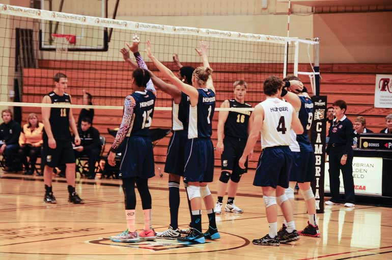 The men's volleyball team at the net ready to resume play. (Photo by Ashleigh Darrach)