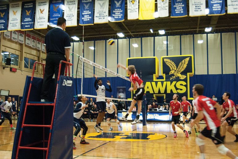 Redeemer's Nico DeBruyne spikes into Humber territory as they defeat the Hawks' men's team in four sets. (Photo by Alexandra Martino)