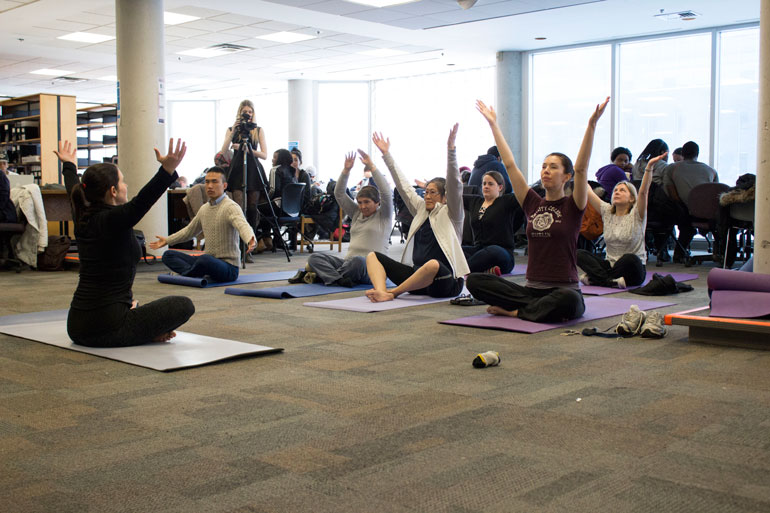 Humber students take a deep breath in while participating in Yoga to relieve stress at Humber's Recess event.