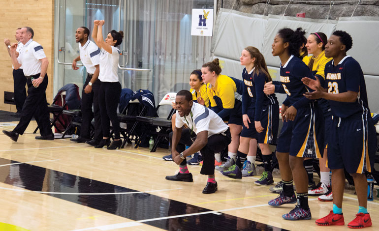 Humber players and coaches react to a late Humber basket in their semi-final win over Algonquin College. (Andy Redding)