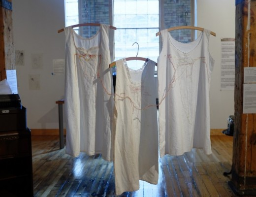 Three shirts memorializing a patient named Grace hang in the exhibit. Grace was admitted to the hospital at age 19 and remained there until she died of pneumonia at age 79. (Photo: Jimmy Kakish)