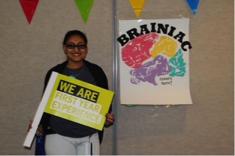 "Davi Lall, who is part of the First Year Experience (FYE) team, stands in front of the popular ""Brainiac"" game. FYE helps new students on campus a number of welcome-oriented events and helps connect freshmen to peer mentors."