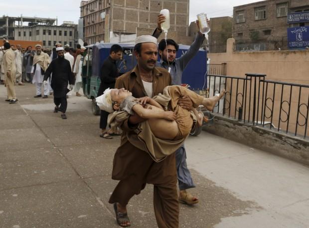 Aid worker carries injured boy to hospital in Peshawar. (Photo: Khuram Parvez/Reuters)