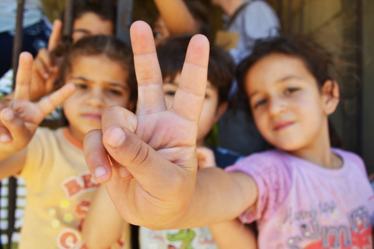 Syrian refugee children at a half-built apartment block near Reyfoun in Lebanon, close to the border with Syria, give the peace sign. The families fled Syria due to the war and are now living on a building site. (Photo: Eoghan Rice, Wikimedia Commons)
