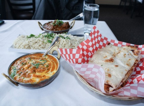 Delicious indian food and naan bread on a dinner table.