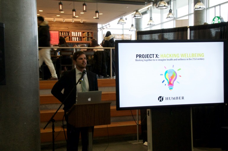 Manager of the Centre of Innovation in Health and Wellness and Project X organizer Matias Golob MCing at event.