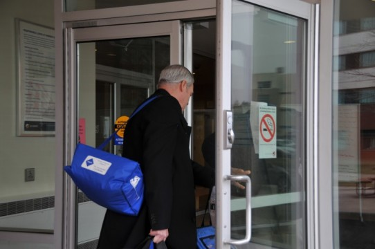 A Toronto Public Health officer enters R building at North campus residence. (Genia Kuypers)